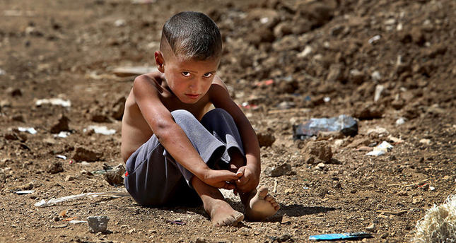 In this Wednesday, Sept. 11, 2013 file photo, A Syrian refugee boy sits on the ground at a temporary refugee camp, in the eastern Lebanese Town of Al-Faour. AP Photo