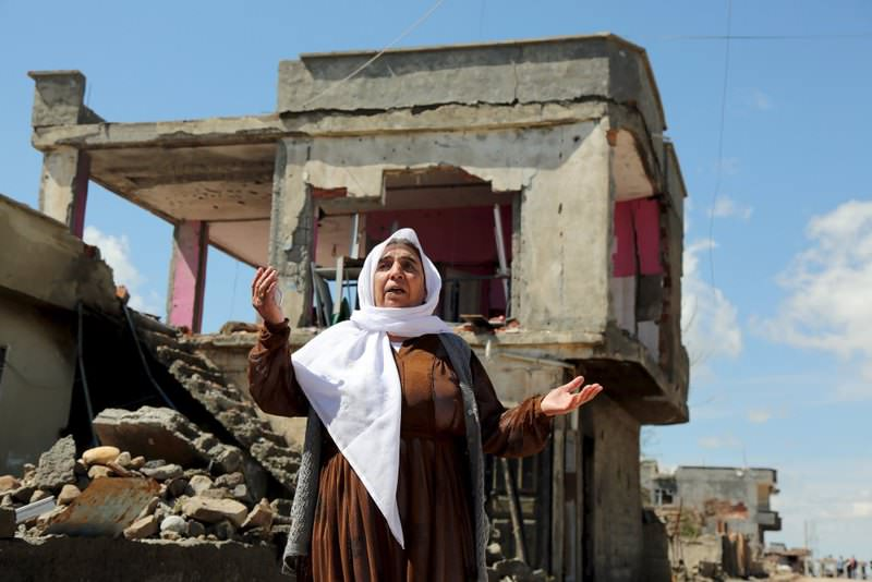 A Kurdish woman reacting as she stands in front of her house, which was damaged by PKK militants, in the southeastern town of Idil, Turkey.