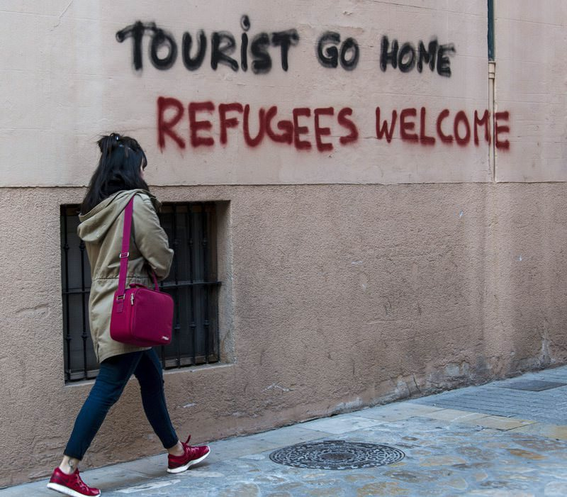 A woman walks next to a grafitti that reads 'Tourist go home, Refugees welcome', in downtown, Palma Majorca, Balearics Islands, Spain, 13 April 2016 (EPA Photo)