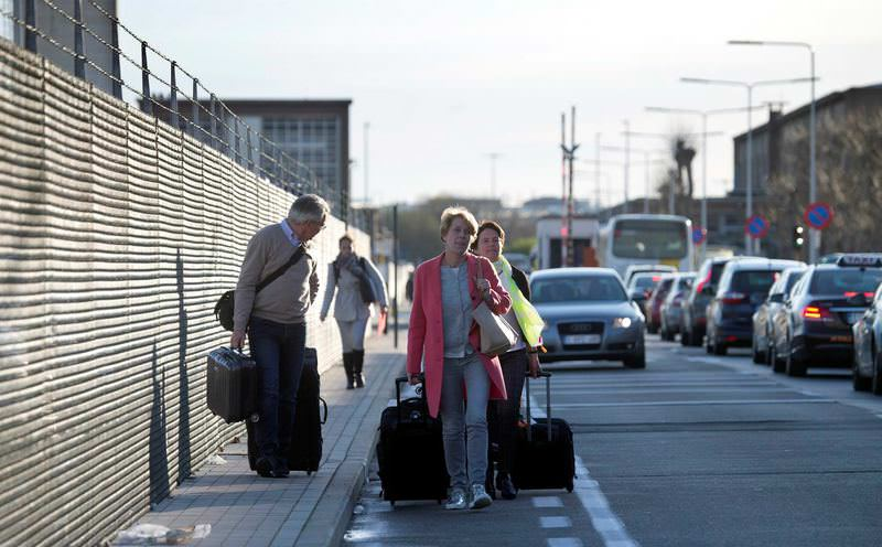 Passengers walk with their luggage on the main road from Zaventem Airport since their flights were canceled.