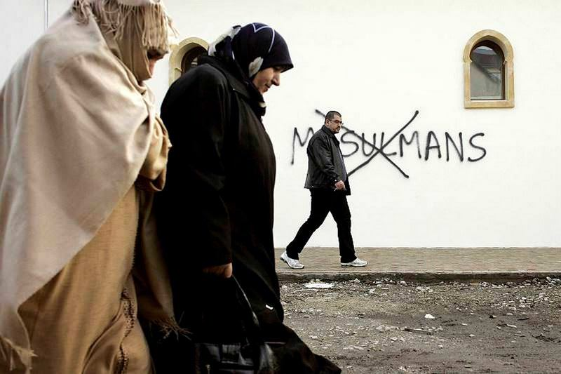 Two Muslim women pass by a wall in Paris on which u2018No Muslims' is written.
