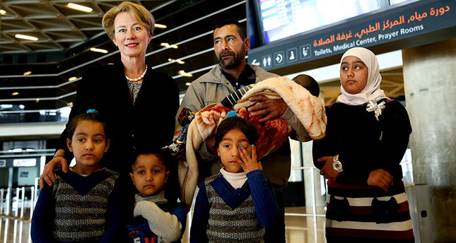 U.S. Ambassador to Jordan Alice Wells, top left, poses for a photo with Syrian refugee Ahmad al-Abboud, top center, and his family at the International Airport of Amman, Jordan, Wednesday, April 6, 2016 (AP Photo)