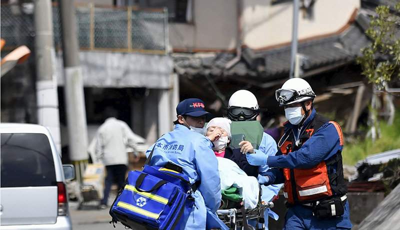 An injured person is carried by rescuers near a damaged house caused by an earthquake in Mashiki town, Kumamoto prefecture, southern Japan, in this photo taken by Kyodo April 15, 2016 (Reuters Photo)