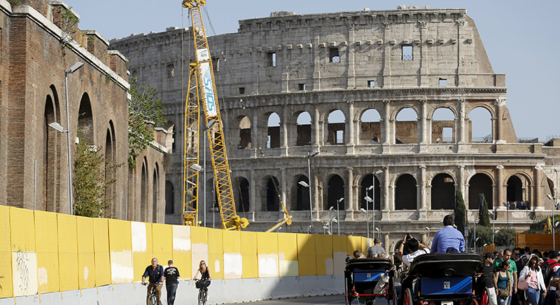 Horse-drawn carriages pass next to a barriers of ,Roma Metropolitane, (Rome's underground) at the Colosseum in Rome, Italy, April 4, 2016 (Reuters Photo)