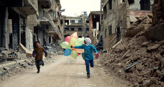Syrian children with balloons running amid heavily damaged buildings in the neighbourhood of Jobar, on the eastern outskirts of the Syrian capital Damascus.