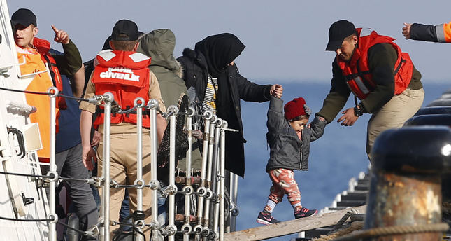 Migrants disembark from a Turkish Coast Guard boat after a failed attempt to cross to Greece.. (Reuters Photo)