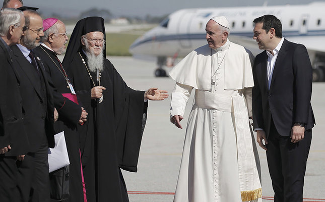 Greek Orthodox Patriarch Bartolomew I (L) and Greek Prime Minister Alexis Trispras (R) welcome Pope Francis as he arrived on the Greek Island of Lesbos, April 16, 2016. (Reuters Photo)