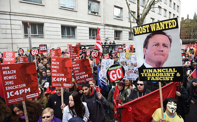 Protestors hold placards during an Anti-Austerity National demonstration in London, Britain, 16 April 2016 (EPA Photo)