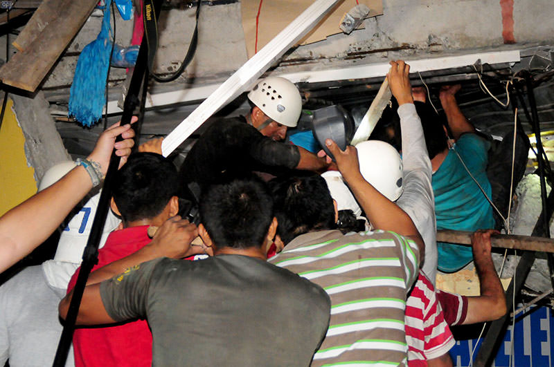 Rescue workers work to pull out survivors trapped in a collapsed building after a huge earthquake struck, in the city of Manta early on April 17, 2016 (AFP)
