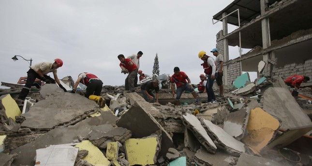 Volunteers search for survivors in the debris of buildings destroyed by an earthquake in Pedernales, Ecuador, Sunday, April 17, 2016. (AP Photo)