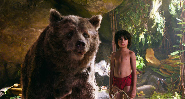 In this image released by Disney, Mowgli, portrayed by Neel Sethi, right, and Baloo the bear, voiced by Bill Murray, appear in a scene from, The Jungle Book. (Disney via AP)