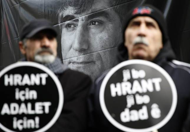 Two men carrying placards reading For Hrant, For Justice at a ceremony to remember the late journalists on Jan. 19, 2016.