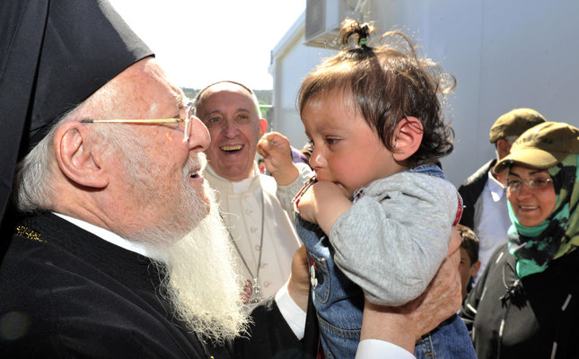 Patriarch Bartholomew (L) lifts a child as Pope Francis looks on during a visit to the Greek island of Lesbos.
