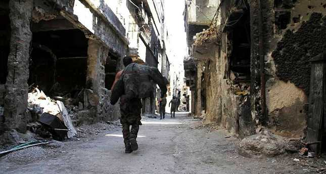 A man walks between damaged buildings in Yarmouk refugee camp, located in a Damascus suburb.
