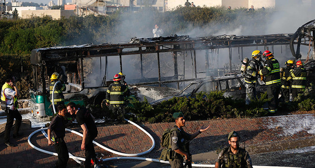 Israeli security forces stand guard as firemen extinguish a burning bus following an attack in Jerusalem on April 18, 2016. AFP Photo