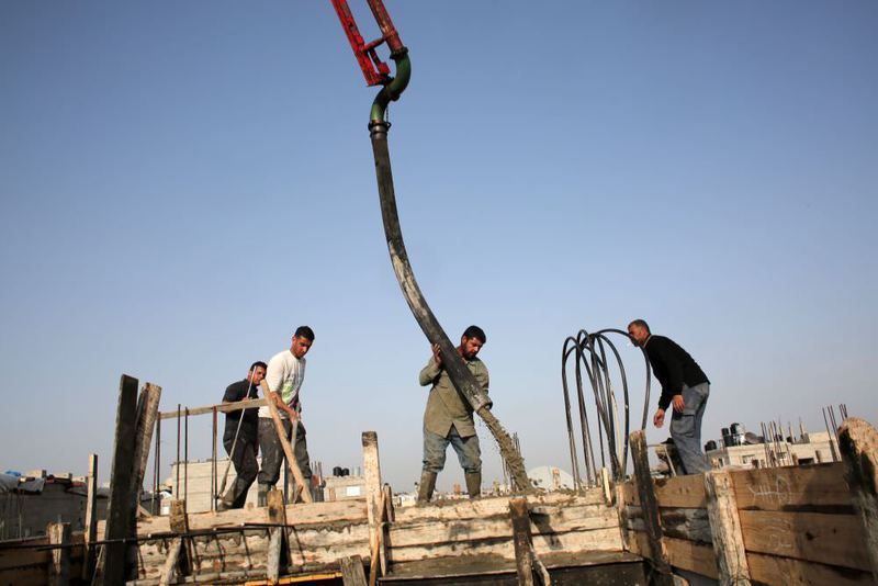 Palestinian workers pour cement on the roof of a building under construction in the southern Gaza Strip town of Rafah. Israel announced it had stopped private imports of cement to the Hamas-run Palestinian enclave.