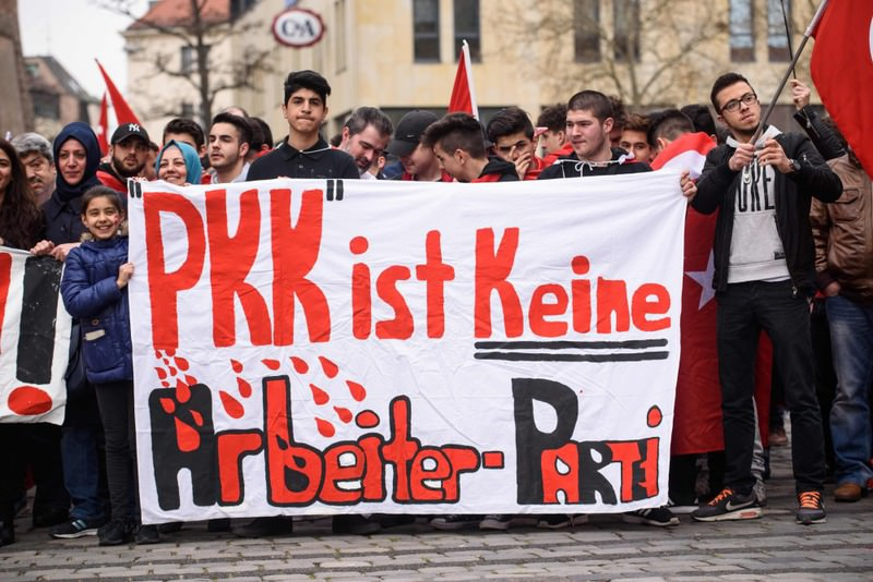 People holding a banner reading ,PKK is not a worker's party, during a ,Peace March for Turkey, organized by the new German Turkish Committee in Nuremberg, Germany.