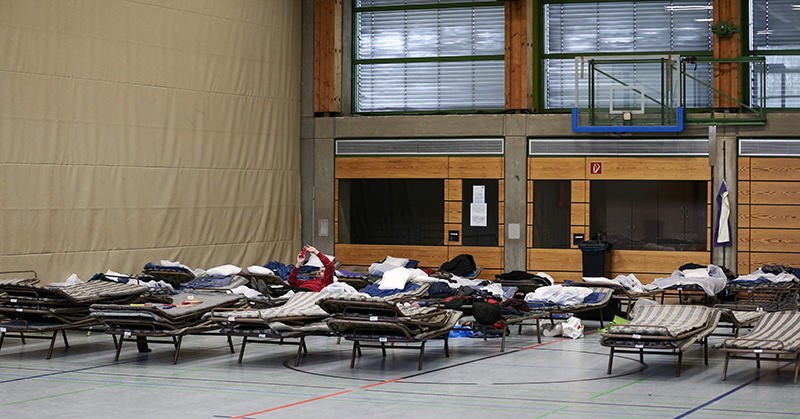 Picture taken on February 19, 2015 shows refugees laying on field beds at the Frankenhalle gym in Neustadt bei Coburg, southern Germany, that was turned into a makeshift shelter for refugees (AFP Photo)