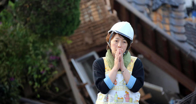 A resident stands in front of damaged house in Mashiki, Kumamoto prefecture, southern Japan.