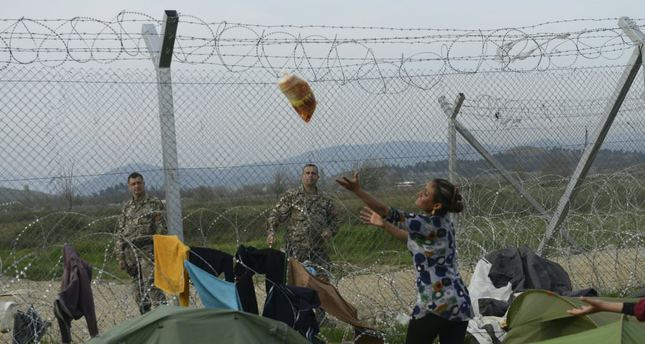 A Macedonian soldier throwing bread to Syrian refugee woman standing behind a fence along the border barrier at the makeshift camp along the Greek-Macedonian border, near the Greek village of Idomeni.