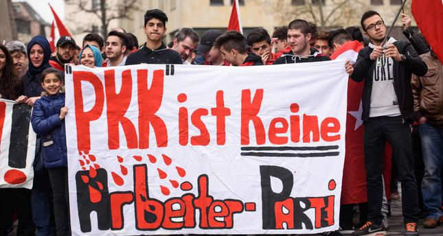 People holding a banner reading PKK is not a worker's party during a Peace March for Turkey organized by the new German Turkish Committee in Nuremberg, Germany.