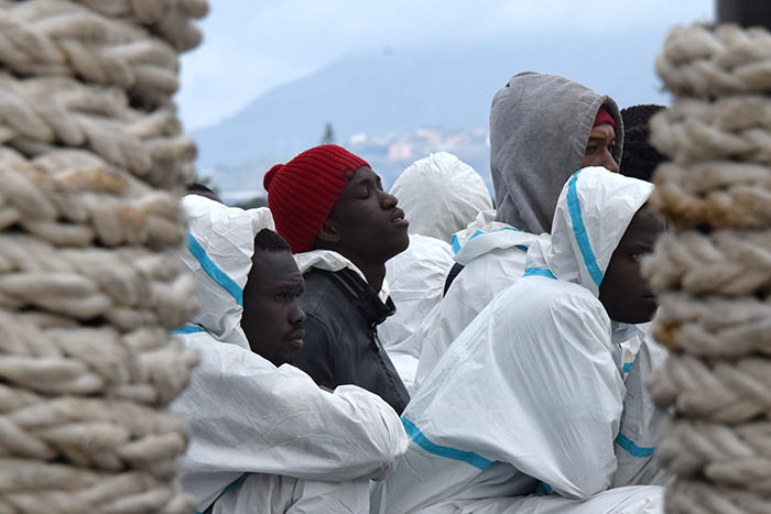This file photo taken on February 1, 2016 shows men waiting to disembark from the Italian Coast Guard vessel ,Dattilo, in the port of Messina, Sicily, following a rescue operation of migrants and refugees at sea (AFP Photo)