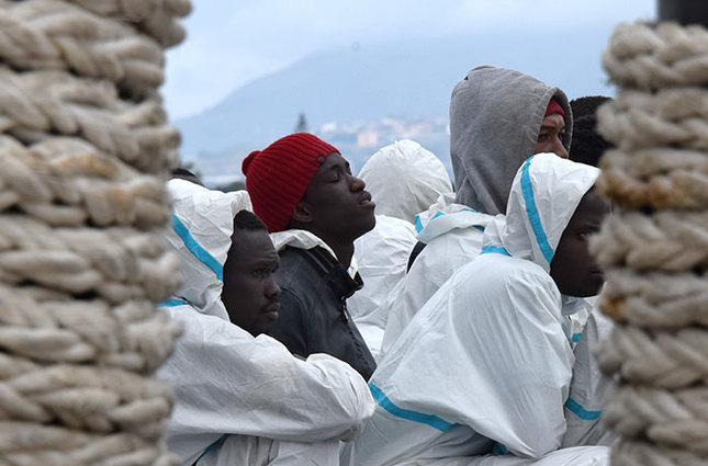 This file photo taken on February 1, 2016 shows men waiting to disembark from the Italian Coast Guard vessel Dattilo in the port of Messina, Sicily, following a rescue operation of migrants and refugees at sea (AFP Photo)