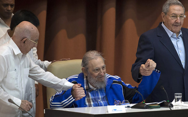 Fidel Castro sits as he clasps hands with his brother, Cuban President Raul Castro, right, and second secretary of the Central Committee, Jose Ramon Machado Ventura. (AP Photo)