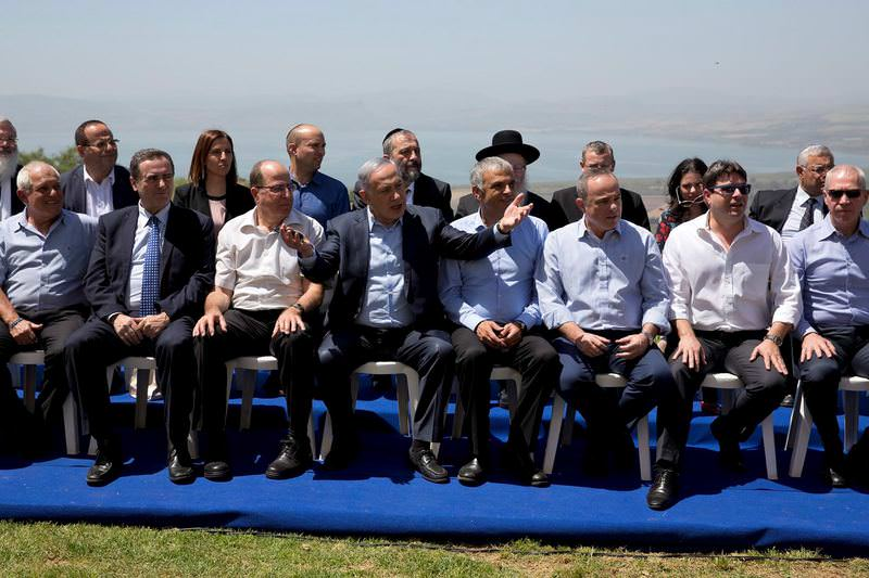 Israeli Prime Minister Benjamin Netanyahu, center, poses with ministers prior to the weekly cabinet meeting in the Israel-controlled Golan Heights.