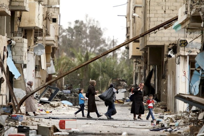 Residents carrying their belongings as they walk during a return visit to the city of Palmyra, Syria.