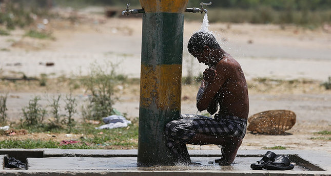 An Indian laborer cools off under a water tap on a hot afternoon in Amritsar, India, 26 May 2015 (EPA Photo)