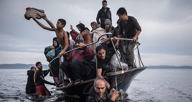 In this Nov. 1, 2015 photo by Sergey Ponomarev, migrants arrive by a Turkish boat near the village of Skala, on the Greek island of Lesbos (AP Photo)