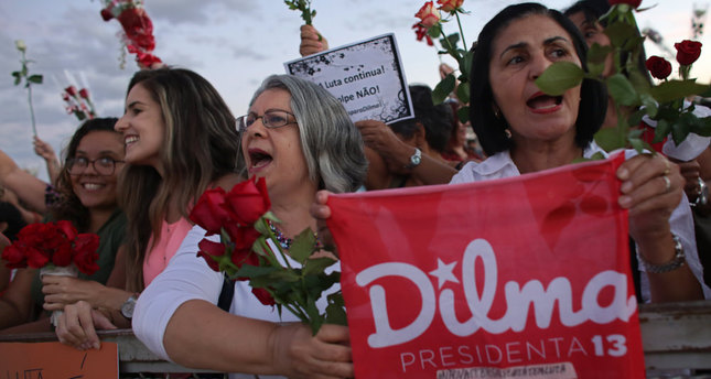 Women carrying flowers take part in Flowers for democracy demonstration against the impeachment process of Brazilian President Dilma Rousseff, in Brasilia.