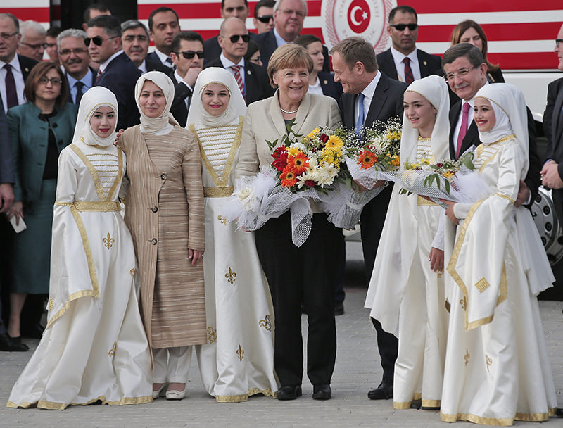 German Chancellor Angela Merkel, centre, accompanied by EU Council President Donald Tusk, 2rd right, Turkish Prime Minister Ahmet Davutou011flu, right, poses for pictures during a visit at the Nizip refugee camp (AP Photo)