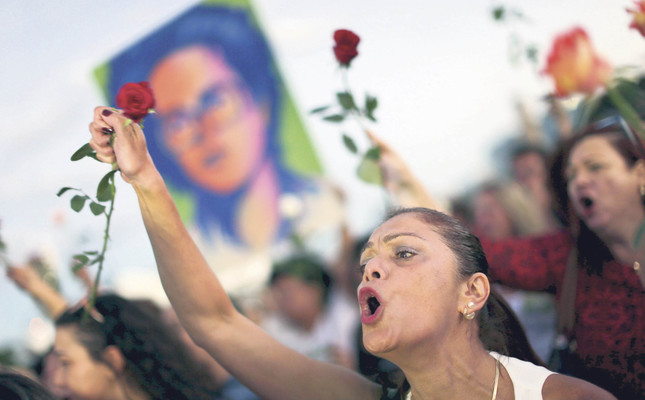 A woman carries flowers in a Flowers for democracy demonstration against the impeachment process of Brazilian President Dilma Rousseff in front of the Planalto Presidential Palace in Brazil.