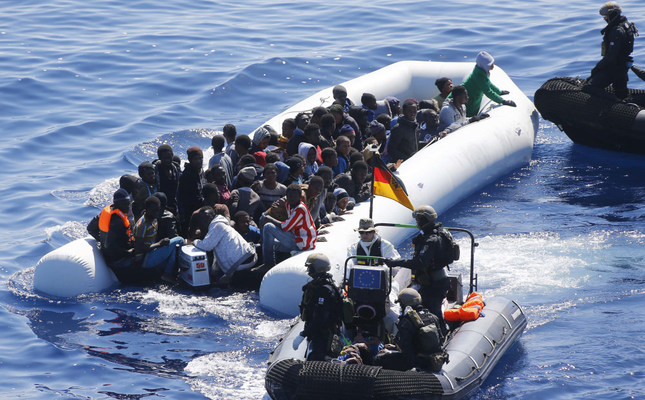 In this March 29,2016 picture, a boat with migrants surrounded by German sailors and Finish special Forces near the German combat supply ship Frankfurt am Main during the EUNAVFOR MED Operation Sophia in the Mediterranean Sea off the coast of Libya.