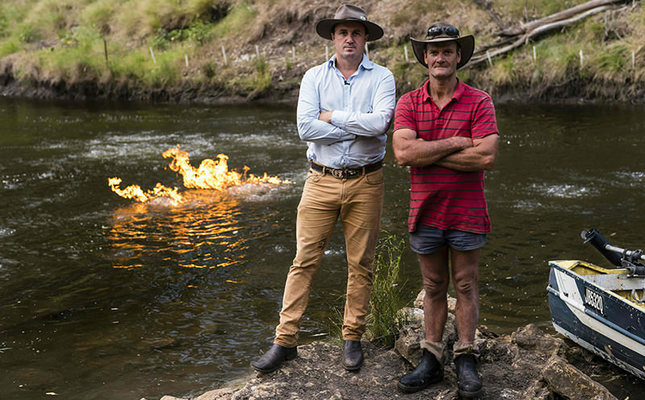 This handout photo from the New South Wales Greens Party taken on April 12, 2016 shows Greens MP Jeremy Buckingham (L) posing with local resident John Jenkyn (R) after he set fire to methane gas along the Condamine River in Queensland. (AFP Photo)