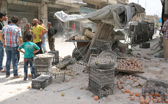 Syrians look at the damage following a reported air strike by regime forces on the rebel-held neighbourhood of Sakhur in the northern city of Aleppo on April 24, 2016. (AFP Photo)
