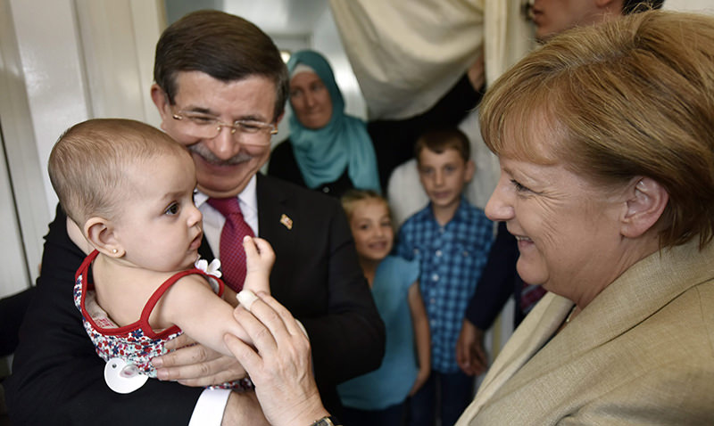 German Chancellor Angela Merkel (R) and Turkish Prime Minister Ahmet Davutou011flu talking to a family of refugees, while Davutou011flu holds the family's youngest child, as they visit the Nizip I refugee camp (EPA Photo)
