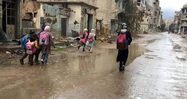Syrian girls walk home from school in the rain in the southwestern city of Daraa, Syria.
