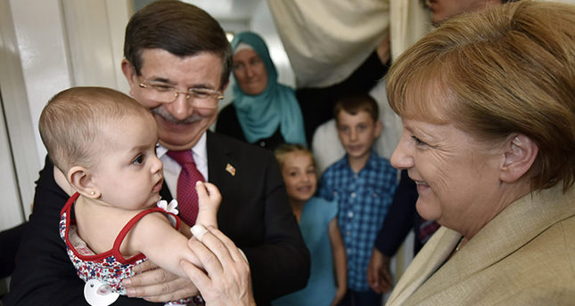 German Chancellor Angela Merkel (R) and Turkish Prime Minister Ahmet Davutoğlu talking to a family of refugees, while Davutoğlu holds the family's youngest child, as they visit the Nizip I refugee camp (EPA Photo)