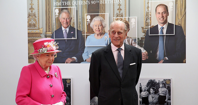 Britain's Queen Elizabeth II (L) and Britain's Prince Philip, Duke of Edinburgh pass a giant photograph taken to be used as part of a series of 10 Royal Mail postage stamps (AFP Photo)