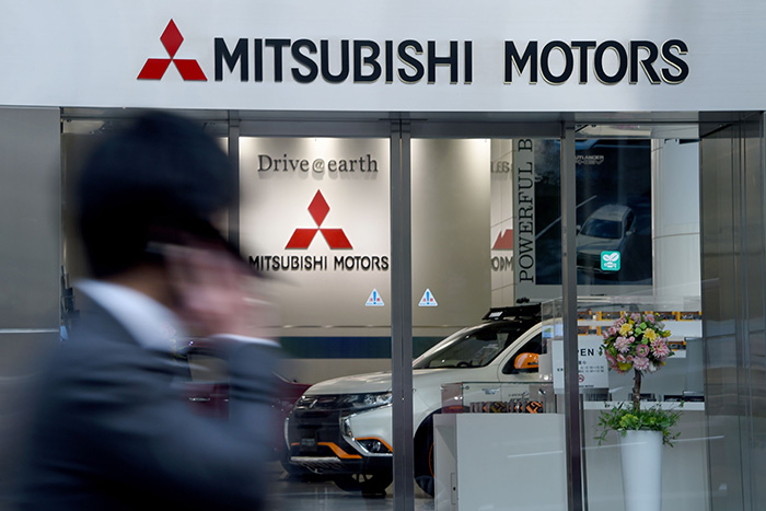 A businessman walks past the Mitsubishi Motors headquarters in Tokyo on April 20, 2016.