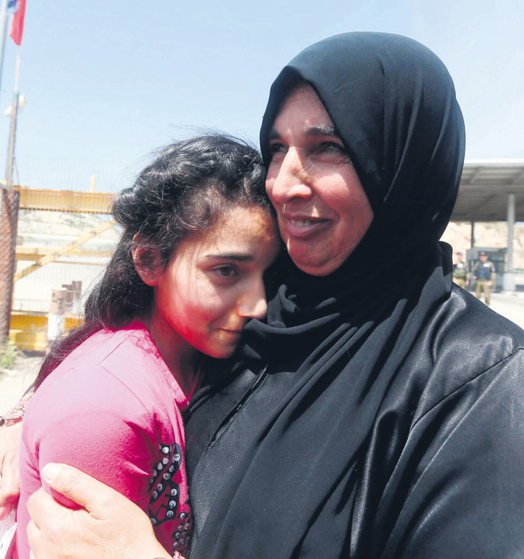 The mother (R) of Palestinian Dima al-Wawi, 12, who is believed to be the youngest female detained by Israel, greets her in the West Bank city of Tulkarem, upon her release from Israeli prison.