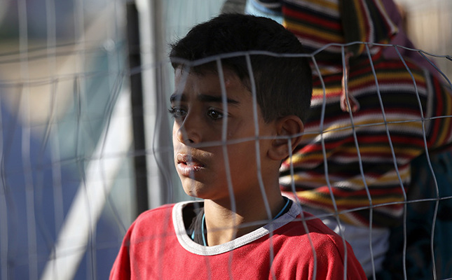 A refugee boy waits for food in the makeshift refugee camp at the northern Greek border point of Idomeni, Greece, Wednesday, March 30, 2016 (AP Photo)