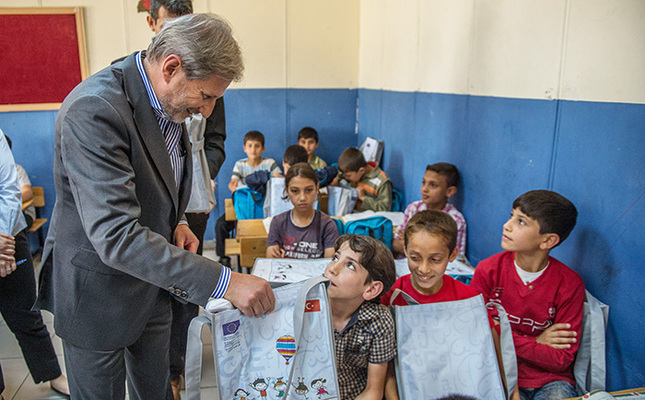 EU Commissioner Johannes Hahn (Center) with refugee children (AA Photo)