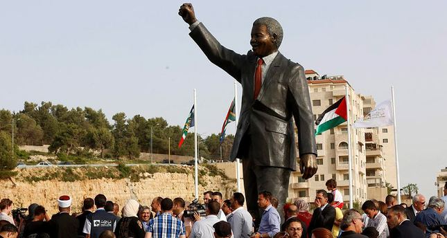 Palestinians and South Africans stand during the revealing of a giant statue of Nelson Mandela in the West Bank city of Ramallah, 26 April 2016. (EPA Photo)