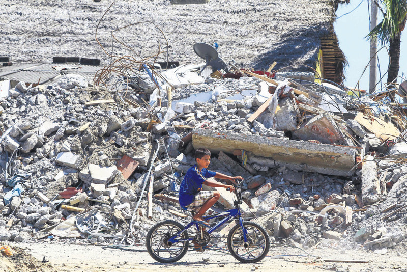 A boy passes by the debris of a building in Canoa, Ecuador. The country experienced its worst earthquake in decades on April 16.