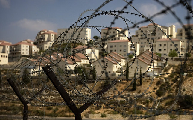 Israeli settlements in occupied West Bank are seen behind the barbed wire (AP Photo)