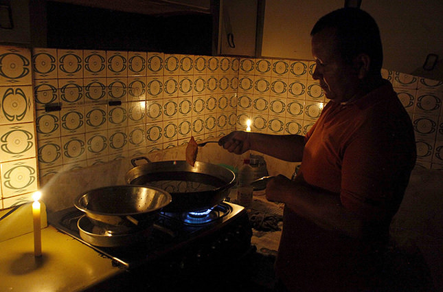 A man cooks lighted by candles lights at his home during a power cut in San Cristobal, in the state of Tachira, Venezuela, April 25, 2016 (Reuters Photo)